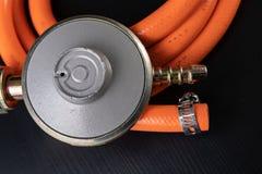 Regolatore per la bombola a gas e gli accessori del propano-butano su una tavola di legno dell'officina Accessori del gas nell'of fotografia stock libera da diritti