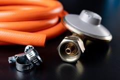 Regolatore per la bombola a gas e gli accessori del propano-butano su una tavola di legno dell'officina Accessori del gas nell'of immagine stock libera da diritti