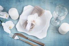 Regolazione d'annata della tavola con le decorazioni dell'orchidea, candele, wineglas Fotografia Stock Libera da Diritti