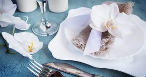 Regolazione d'annata della tavola con le decorazioni dell'orchidea, candele, wineglas Immagini Stock