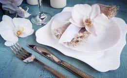 Regolazione d'annata della tavola con le decorazioni dell'orchidea su un fondo blu tinto Fotografia Stock Libera da Diritti