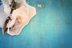 Regolazione d'annata della tavola con le decorazioni dell'orchidea, tovaglioli, wineglas Fotografia Stock Libera da Diritti