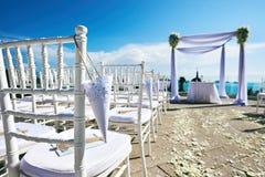 Regolazione della sede di nozze sulla decorazione della collina, dell'arco e dell'altare, sedie bianche con il cono della rosa de Immagine Stock