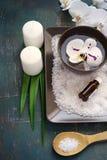 Regolazione della STAZIONE TERMALE con i fiori dell'orchidea e sale marino e candele bianchi Immagine Stock