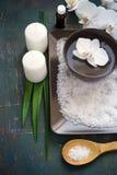 Regolazione della STAZIONE TERMALE con i fiori dell'orchidea e sale marino e candele bianchi Fotografia Stock