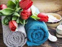 Regolazione della stazione termale con i tulipani rossi e gli asciugamani molli del cotone Fotografia Stock