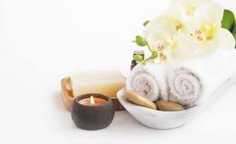 Regolazione della stazione termale con il fiore, la candela, il sapone e gli asciugamani dell'orchidea su briciolo Fotografia Stock
