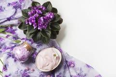 Regolazione della stazione termale con la crema cosmetica, il sale da bagno e la viola africana in vaso di fiore sul fondo di leg Immagini Stock