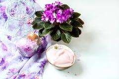 Regolazione della stazione termale con la crema cosmetica, il sale da bagno e la viola africana in vaso di fiore sul fondo di leg Fotografia Stock Libera da Diritti