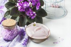 Regolazione della stazione termale con la crema cosmetica, il sale da bagno e la viola africana in vaso di fiore sul fondo di leg Immagini Stock Libere da Diritti