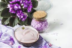 Regolazione della stazione termale con la crema cosmetica, il sale da bagno e la viola africana in vaso di fiore sul fondo di leg Fotografie Stock Libere da Diritti