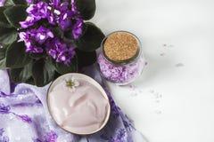 Regolazione della stazione termale con la crema cosmetica, il sale da bagno e la viola africana in vaso di fiore sul fondo di leg Immagine Stock