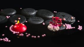 Regolazione della stazione termale del fiore di cambria dell'orchidea sulle pietre di zen con le gocce Fotografia Stock