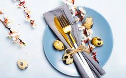 Regolazione della Tabella di Pasqua con le uova ed i rami di quaglia in fiore, fondo di feste della primavera fotografia stock