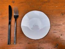 Regolazione della Tabella sul legno - coltello, forcella e un piatto immagini stock libere da diritti