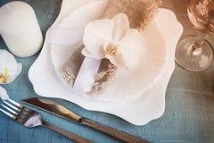 Regolazione della tavola della primavera con le decorazioni dell'orchidea, candele, bicchiere di vino Immagini Stock Libere da Diritti