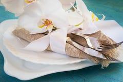 Regolazione della tavola della primavera con le decorazioni dell'orchidea ed i tovaglioli bianchi o Immagine Stock