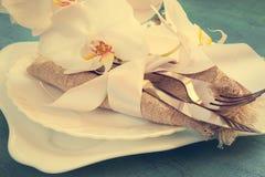 Regolazione della tavola della primavera con le decorazioni dell'orchidea ed i tovaglioli bianchi o Fotografia Stock Libera da Diritti