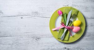 Regolazione della tavola di Pasqua con i fiori e la coltelleria della molla immagini stock libere da diritti
