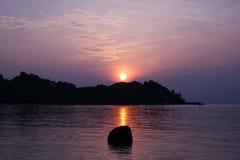 Regolazione dorata del sole dietro l'isola nell'oceano Immagine Stock