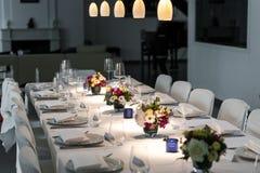 Regolazione elegante della tavola con i punti luminosi ed i fiori fotografia stock