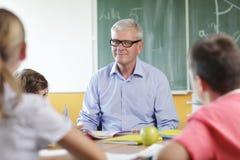 Regolazione elementare dell'aula. Fuoco sull'insegnante e sulla lavagna. Fotografie Stock Libere da Diritti