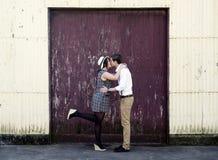 Regolazione industriale baciante delle retro dell'anca dei pantaloni a vita bassa coppie romantiche di amore Fotografia Stock Libera da Diritti