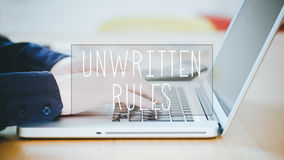 Regole non scritte, testo sopra il giovane che scrive sul computer portatile allo scrittorio Fotografie Stock Libere da Diritti