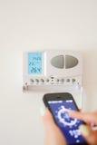 Regoli la temperatura nell'interno domestico con lo smartphone fotografia stock libera da diritti