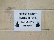 Regoli prego le manopole prima della regolazione del segno di altezza con la borsa di pugilato sulla parete fotografie stock libere da diritti