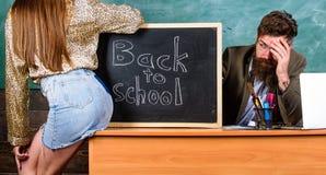 Regras da disciplina e do comportamento da escola O professor indignante senta o fundo do quadro da tabela A menina do estudante  foto de stock royalty free