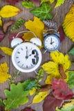 Regredice il cambiamento di tempo Orologi d'annata sul fondo delle foglie di autunno Immagine Stock