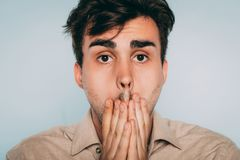 Regret remorse sad distraught man mouth emotion. Regret and remorse. sad distraught man covering mouth with hand. portrait of a young brunet guy on light royalty free stock image