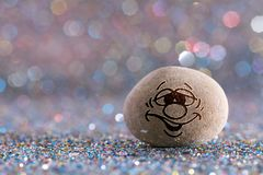 The regret stone emoji. Emotions on color glitter boke background Royalty Free Stock Photo