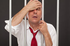 Regretful businessman in prison Stock Photo