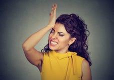 regrets Femme idiote, giflant la main sur la tête ayant duh le moment photos stock