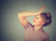 Regrets wrong doing. Silly woman, slapping hand on head having duh moment Royalty Free Stock Images