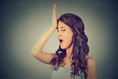 Regrets wrong doing. Woman, slapping hand on head having duh moment Stock Photo