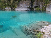 Regroupement bleu entouré par des roches Photos stock