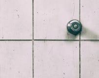 Regue o botão da aba da água na parede suja das telhas do toalete foto de stock