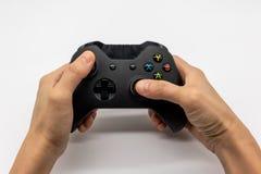 Regulador de consola del videojuego en manos del videojugador Palanca de mando del control de la mano nueva aislada en blanco fotografía de archivo