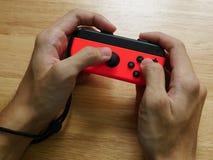 Regulador de interruptor de Nintendo sostenido en manos Foto de archivo