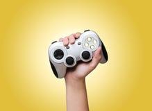 Regulador del juego a disposición criado para arriba sobre amarillo Fotos de archivo