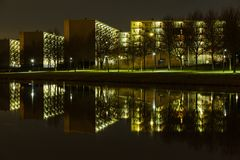 Appartement building and the reflection of it. These regular apparatement buildings stand next to the canal called Zuid Willemsvaart in Helmond city. At night stock images