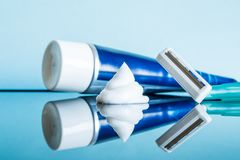 Regular disposable razor and shaving cream in a modern bathroom on a glass reflective surface against a blue background.  stock image