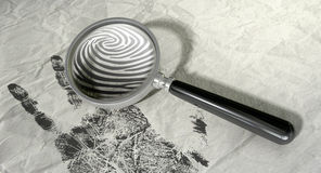 Magnifying Glass And Fingerprint. A regular magnifying glass magnifyng the fingerprint of a hand print on a crumpled paper Stock Photo