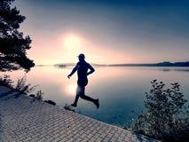 Regular run at lake. Man runner sprinting outdoor in scenic nature stock image