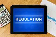 Regulation word on digital tablet Stock Photography