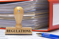 Regulations. Marked on rubber stamp with folder and contract documents royalty free stock photos