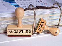 Regulations and Rules - two stamps in the office. Regulations and Rules - two wooden stamps with binder in the office royalty free stock image